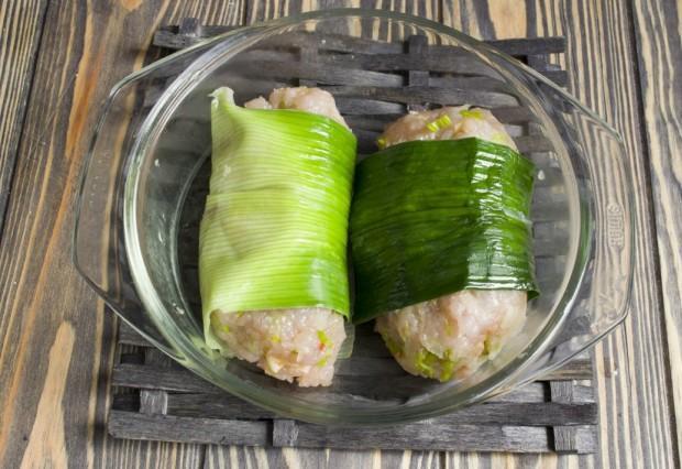 Оборачиваем котлеты размягченными листьями порея и ставим готовиться в микроволновую печь