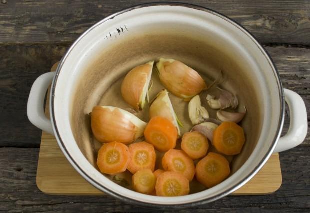 В кастрюлю выкладываем морковь, лук и чеснок