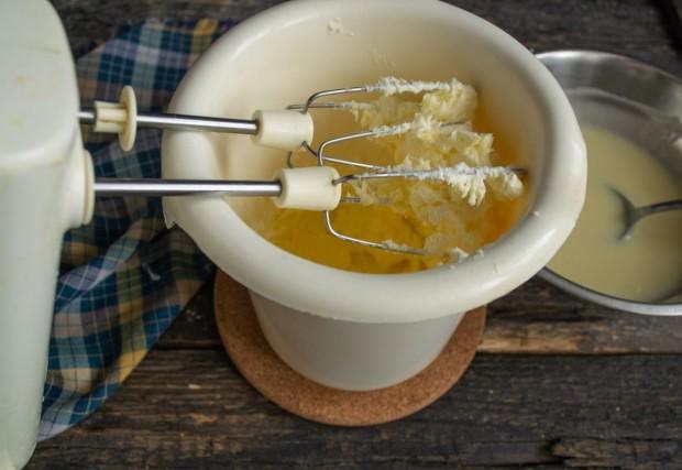 Добавляем размягченное сливочное масло и взбиваем до образования пышной белой массы